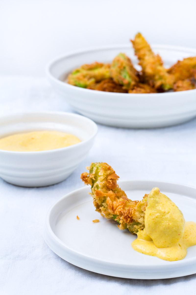 Knuspriger Avocado Wedge auf kleinem Teller mit Mango-Curry-Dip