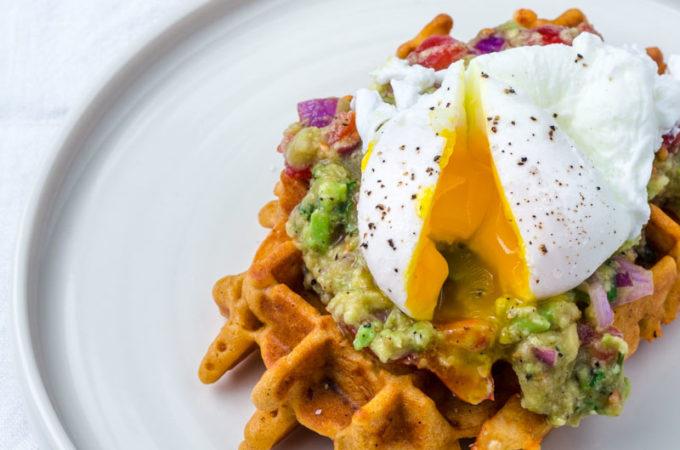 Aufgeschnittenes pochiertes Ei läuft über Cornbread Waffel