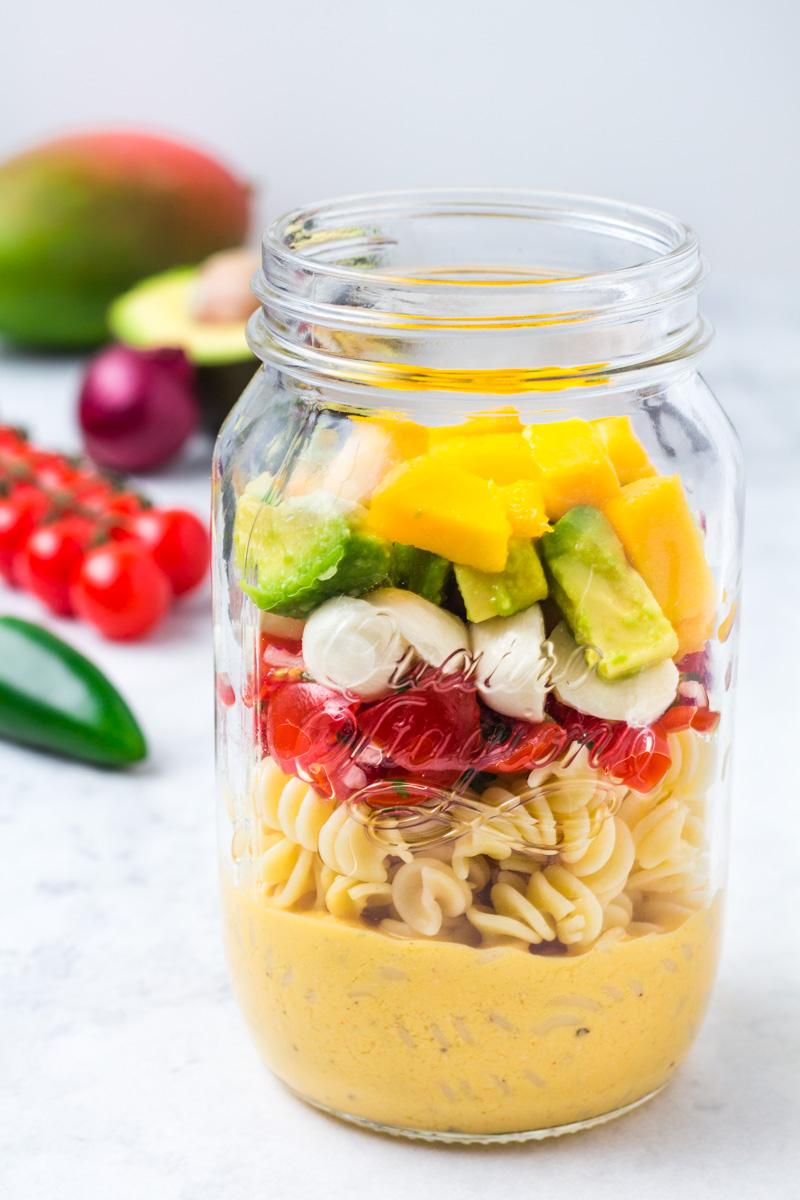 Im Glas geschichteter Nudelsalat mit Avocado-Mango-Tomate und Mangodressing