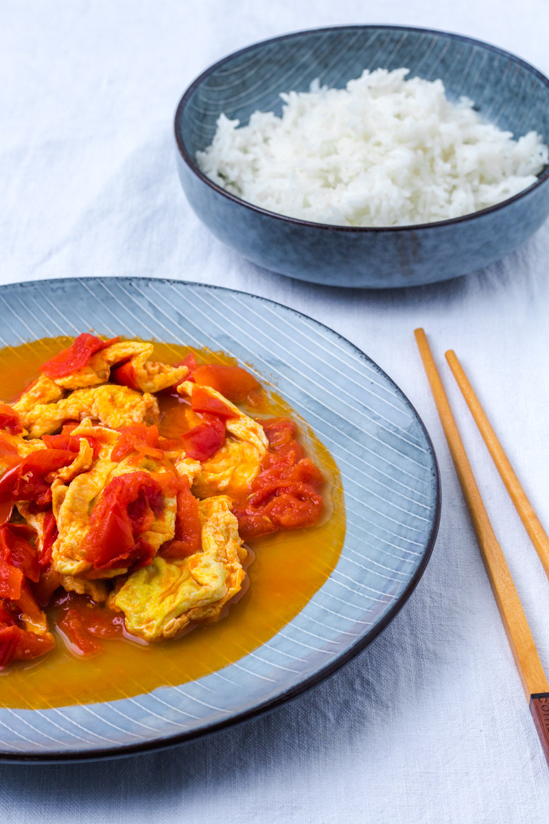 Chinesisches Ruehrei mit gebratenen Tomaten und Reis und Stäbchen
