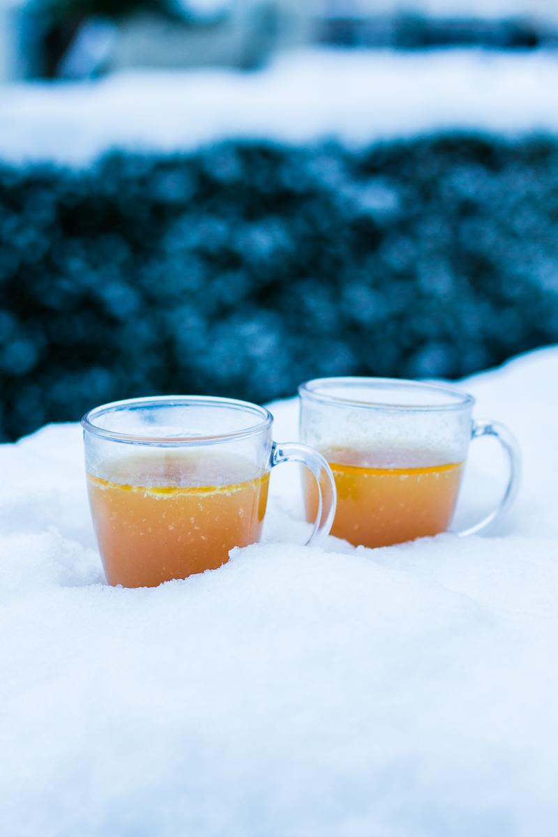 Zwei Gläser Hot Buttered Rum im Schnee