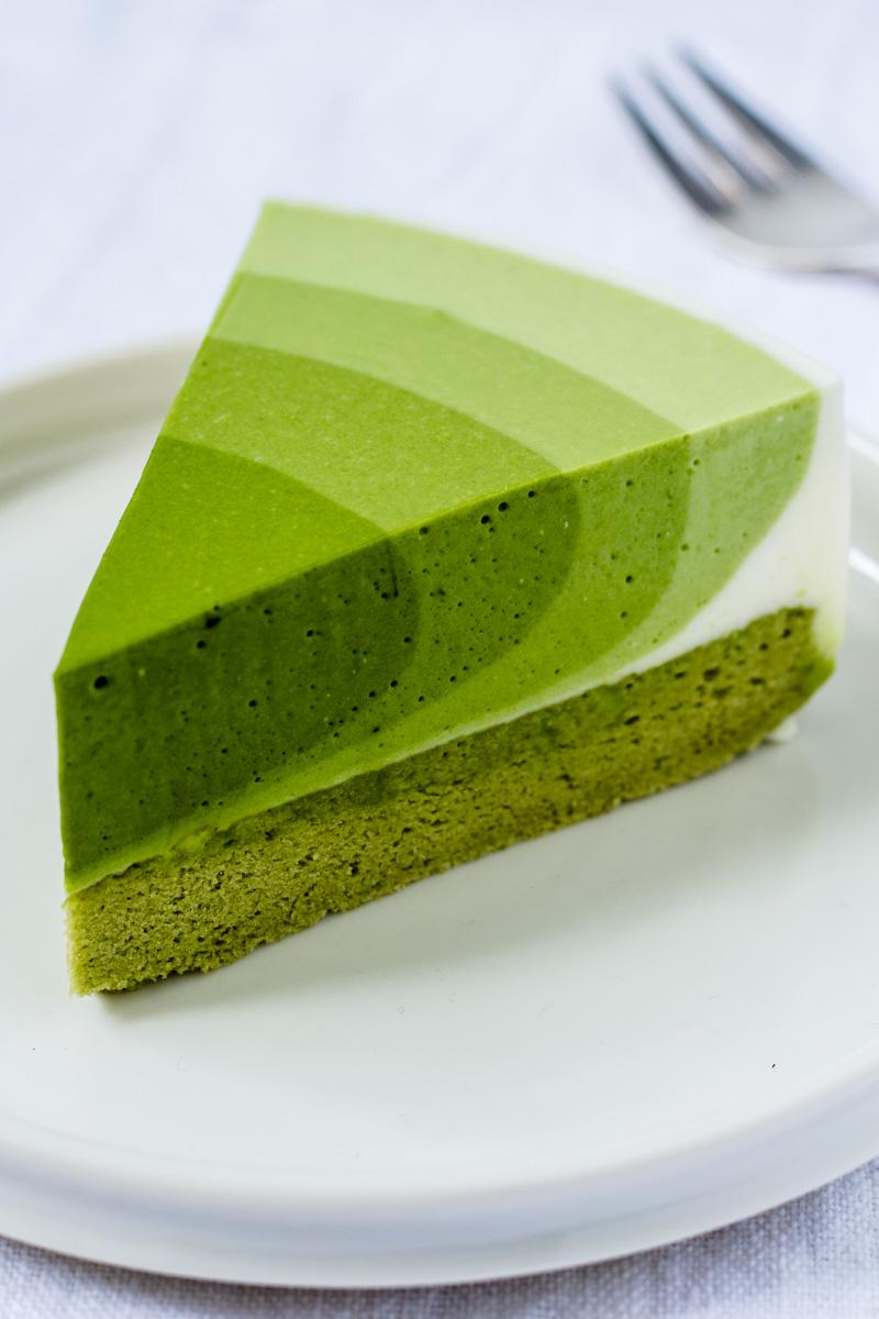Stück Matcha Mousse Kuchen auf kleinem Teller