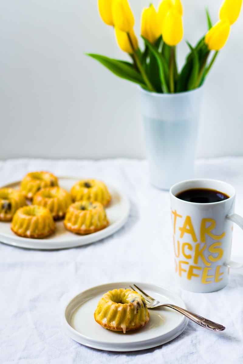 Mini Eierlikör-Gugelhupfe mit einer Tasse Kaffee und gelben Tulpen