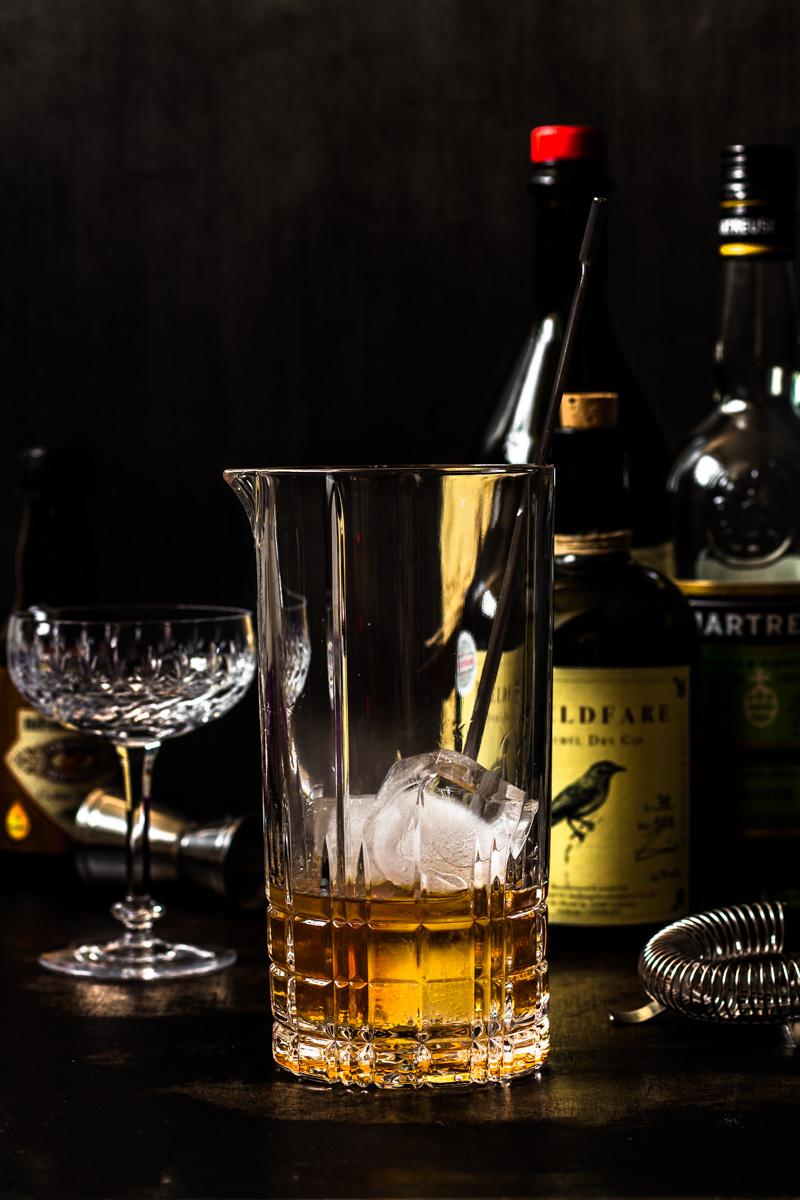 Rührglas mit Eis und Gin, Wermut und Chartreuse