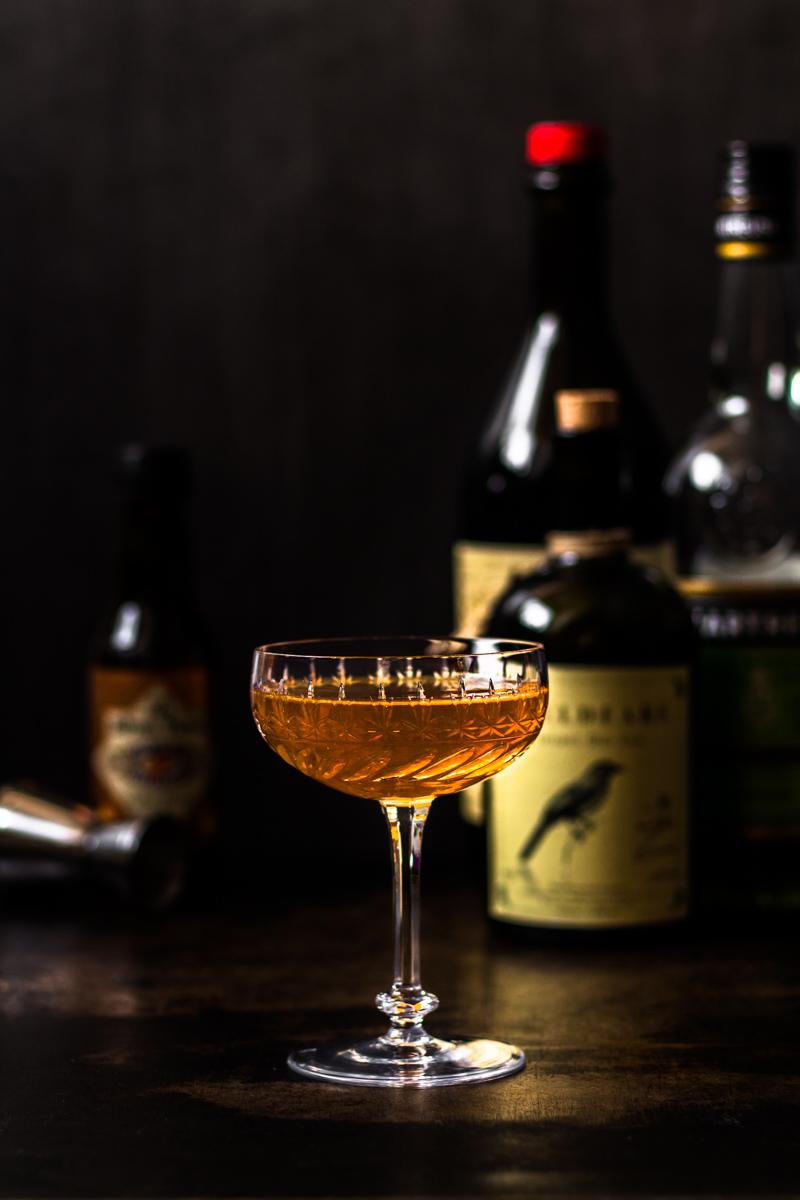 Glas mit Bijou Cocktail und Flaschen