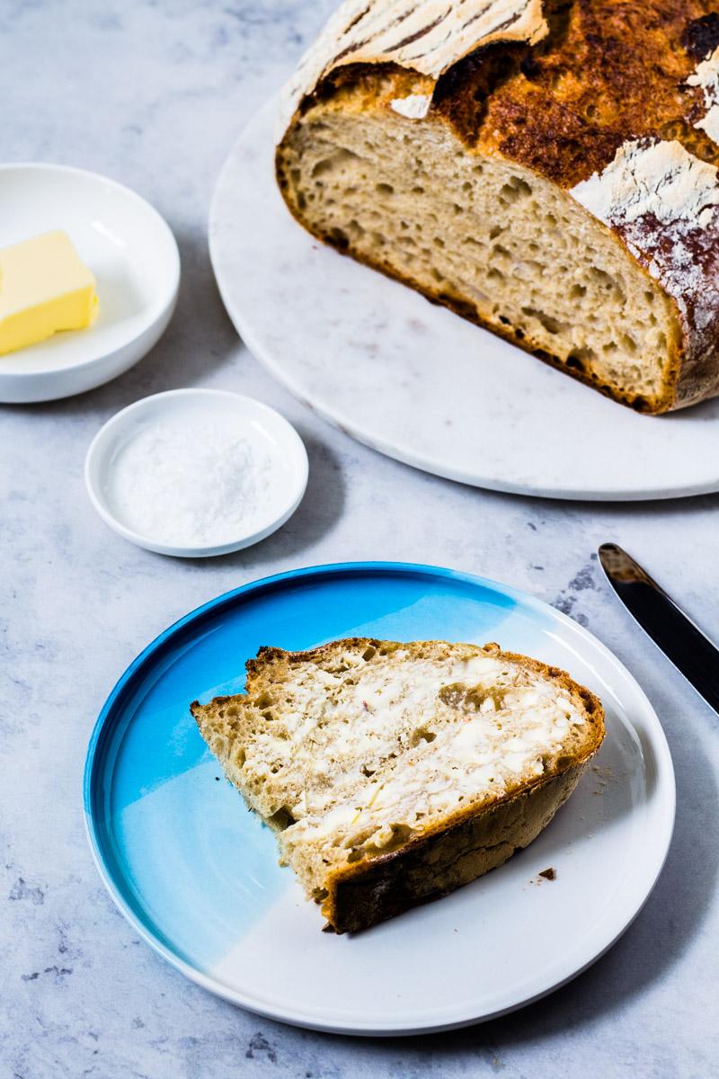 Halbe Scheibe No Knead Bread mit Butter auf kleinem Teller