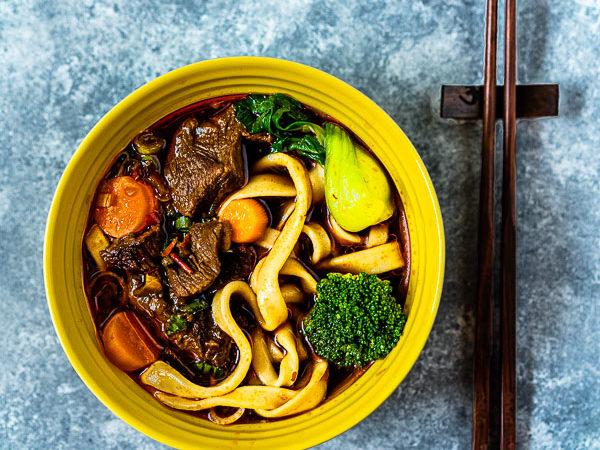 Gelbe Le Creuset Schale mit chinesischer Rindersuppe und handgezogenen Nudeln und Stäbchen