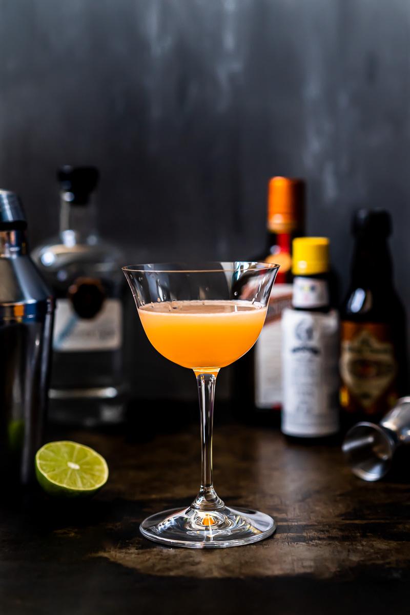 Glas mit Pegu Club Cocktail und den benötigten Zutaten im Hintergrund