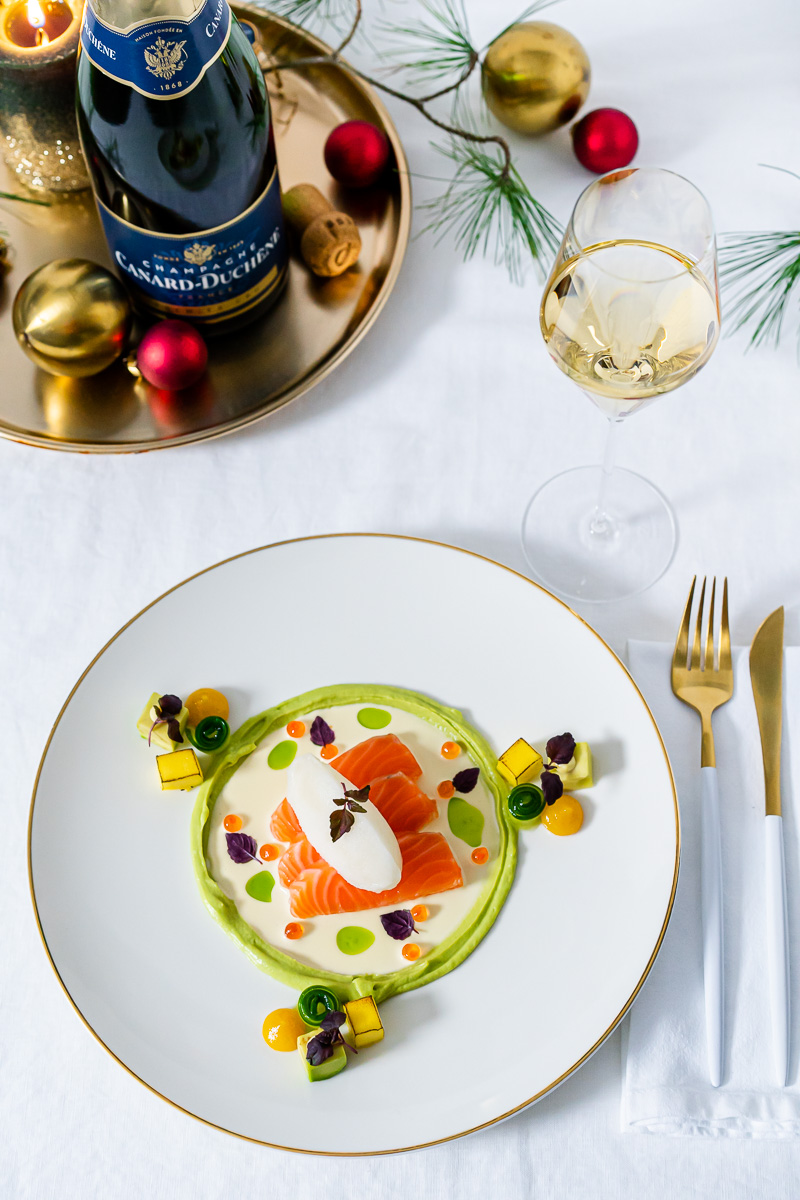 Angerichteter Teller mit Lachs und dazu ein Glas Champagner