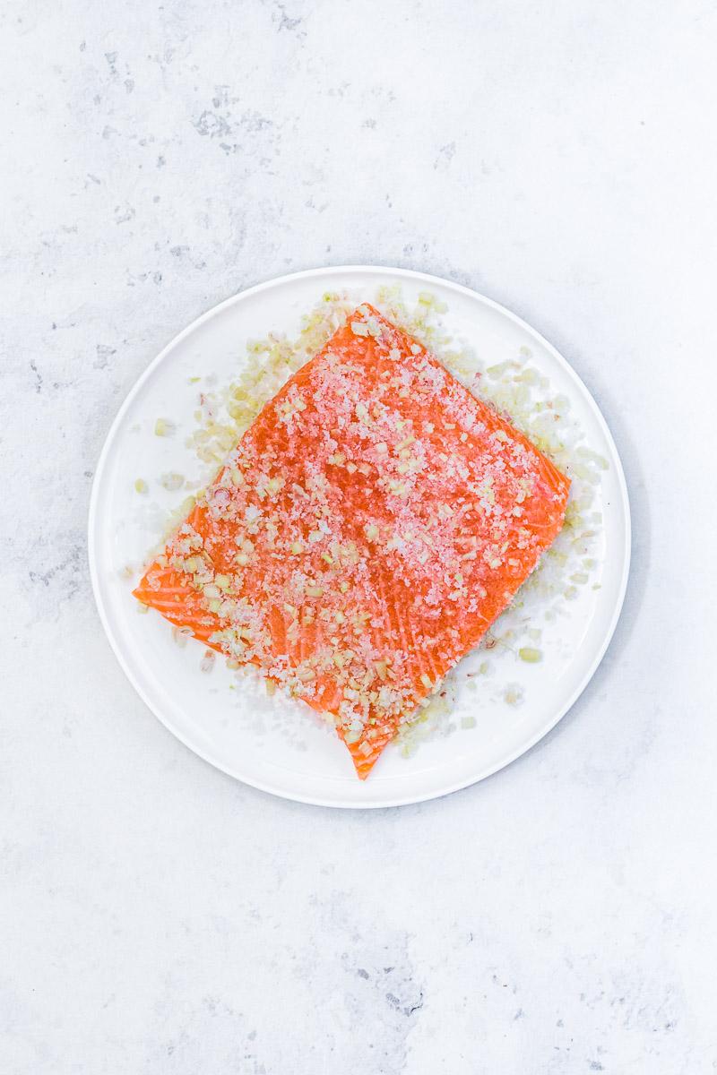 Stück Lachs bedeckt von einer Zitronengras-Salz-Zucker Mischung
