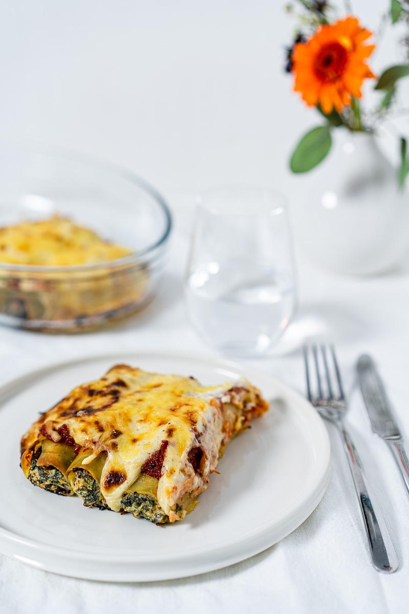 Eine Portion Spinat-Ricotta-Cannelloni auf einem Teller