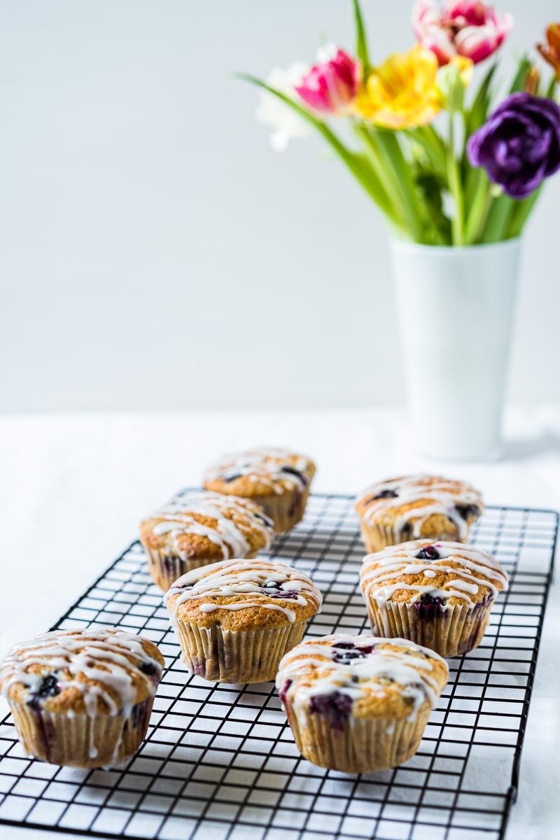Zitronen-Blaubeer-Joghurt Muffins auf Kuchengitter mit Blumen