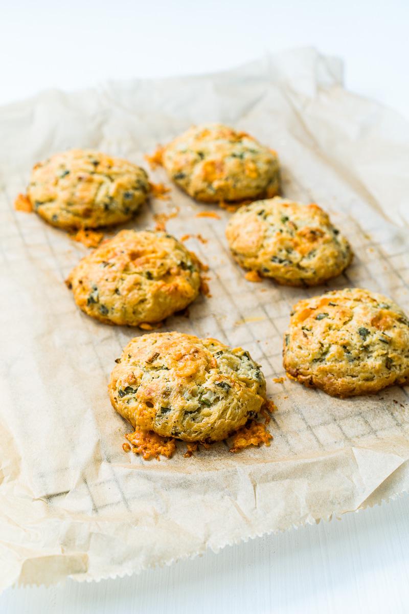 Herzhafte Käse-Frühlingszwiebel Biscuits nach dem Backen auf Backpapier