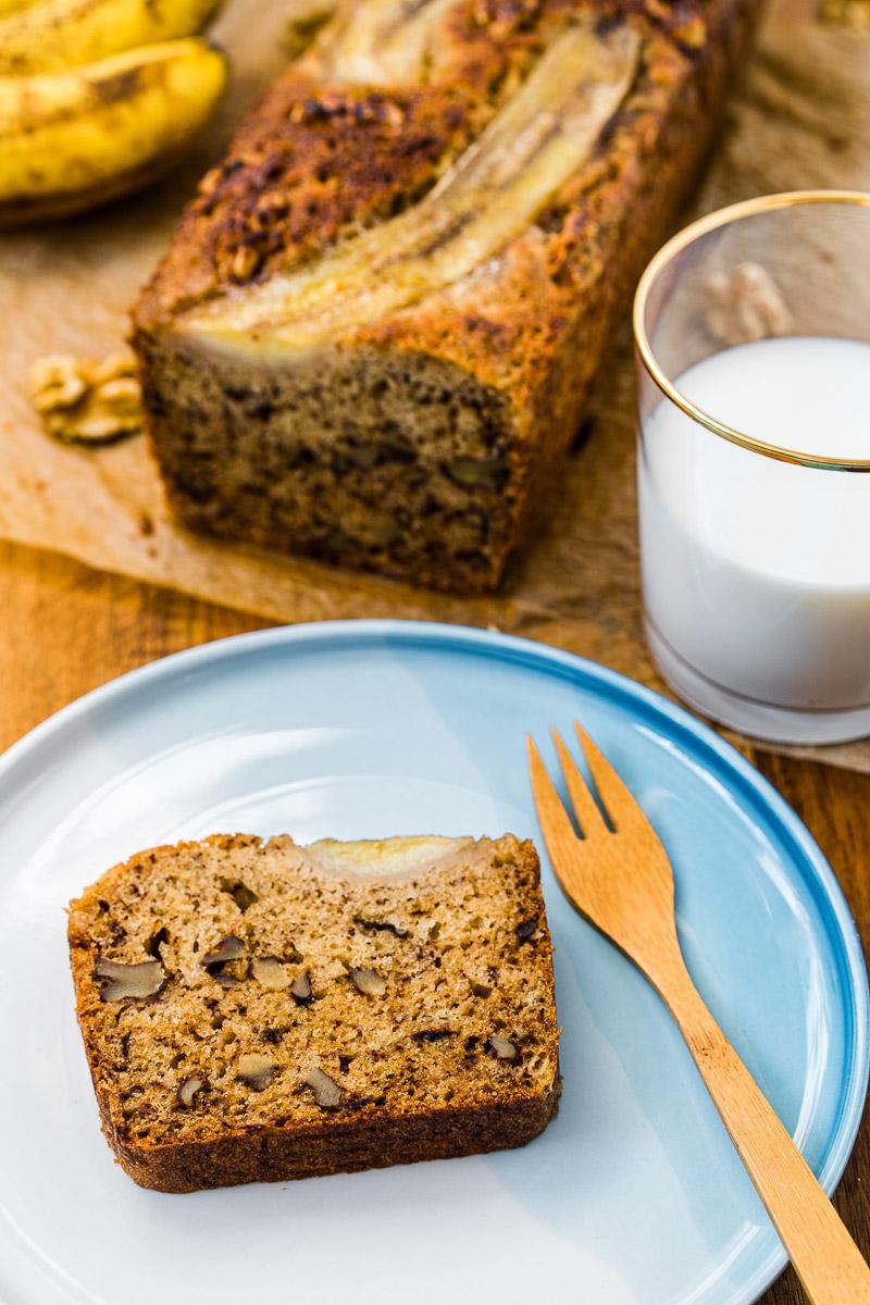 Scheibe Bananenbrot liegt auf Teller mit Kuchengabel und dazu ein Glas Milch