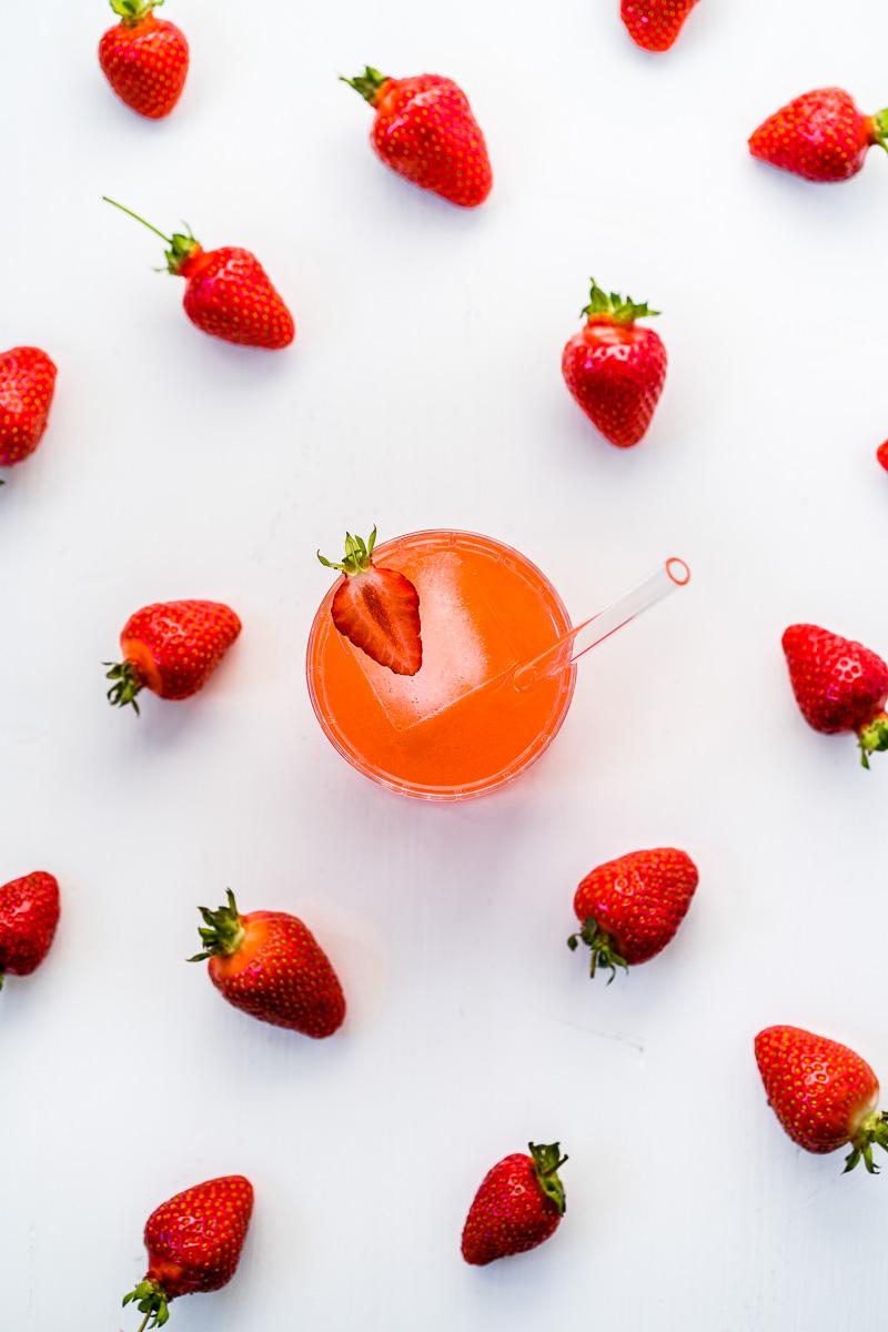 Glas Erdbeer-Gin Sour steht inmitten von Erdbeeren