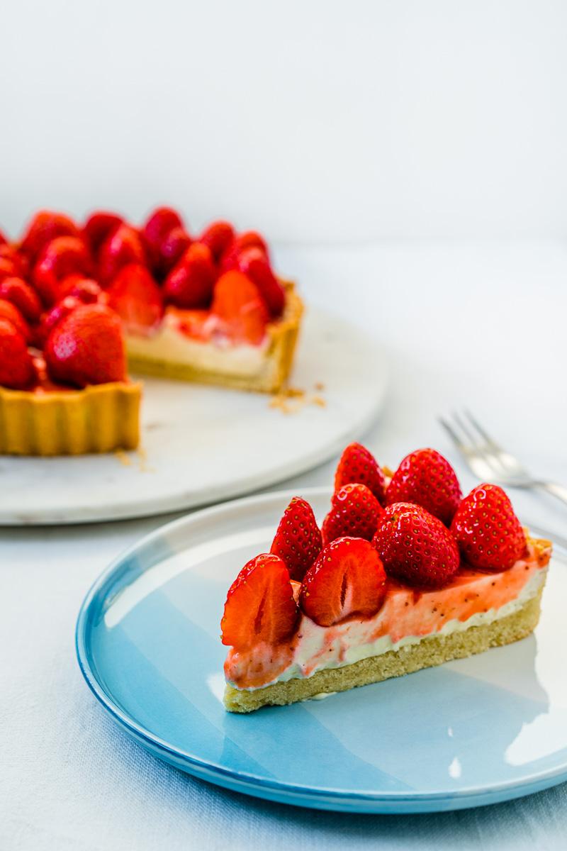 Stück Erdbeer-Tarte mit Lemon Curd-Mascarpone Creme auf Kuchenteller