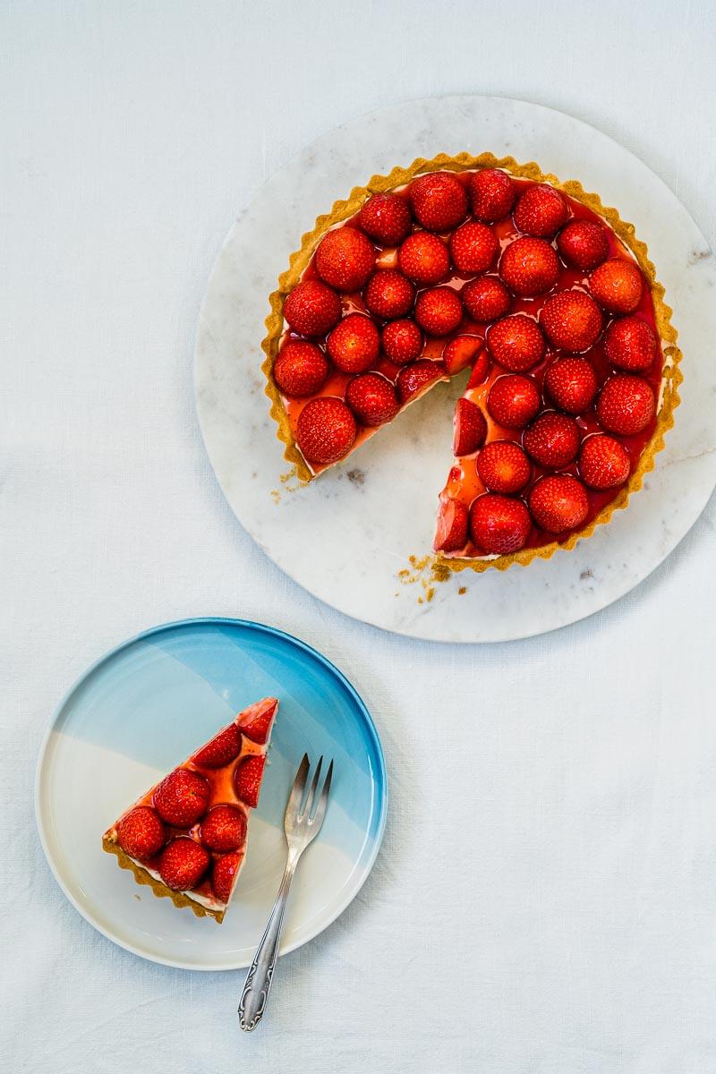 Kleiner Teller mit Stück Erdbeer-Tarte und Tarte auf Marmorplatte
