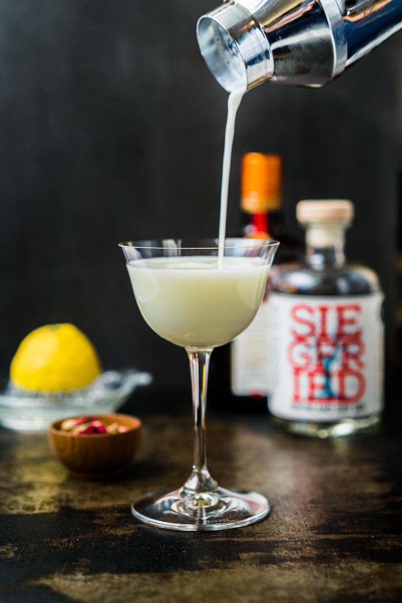 Drink wird aus einem Shaker in ein Sour Glas abgeseiht