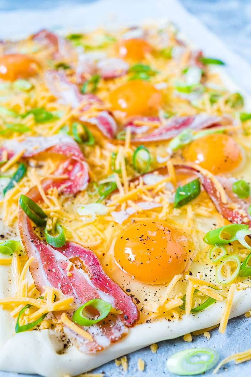 Ei, Bacon, Käse und Frühlingszwiebeln auf Blätterteig in Nahaufnahme