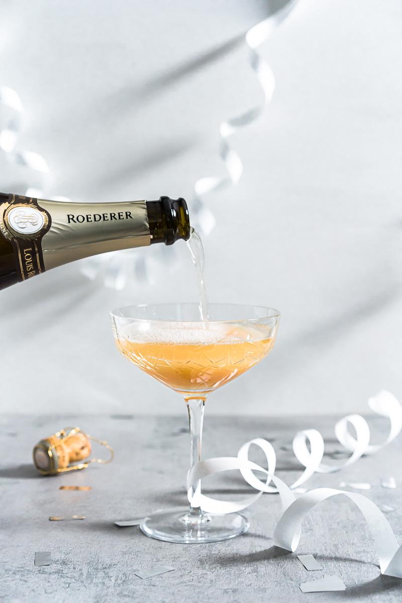In Cocktailschale wird Champagner gegossen