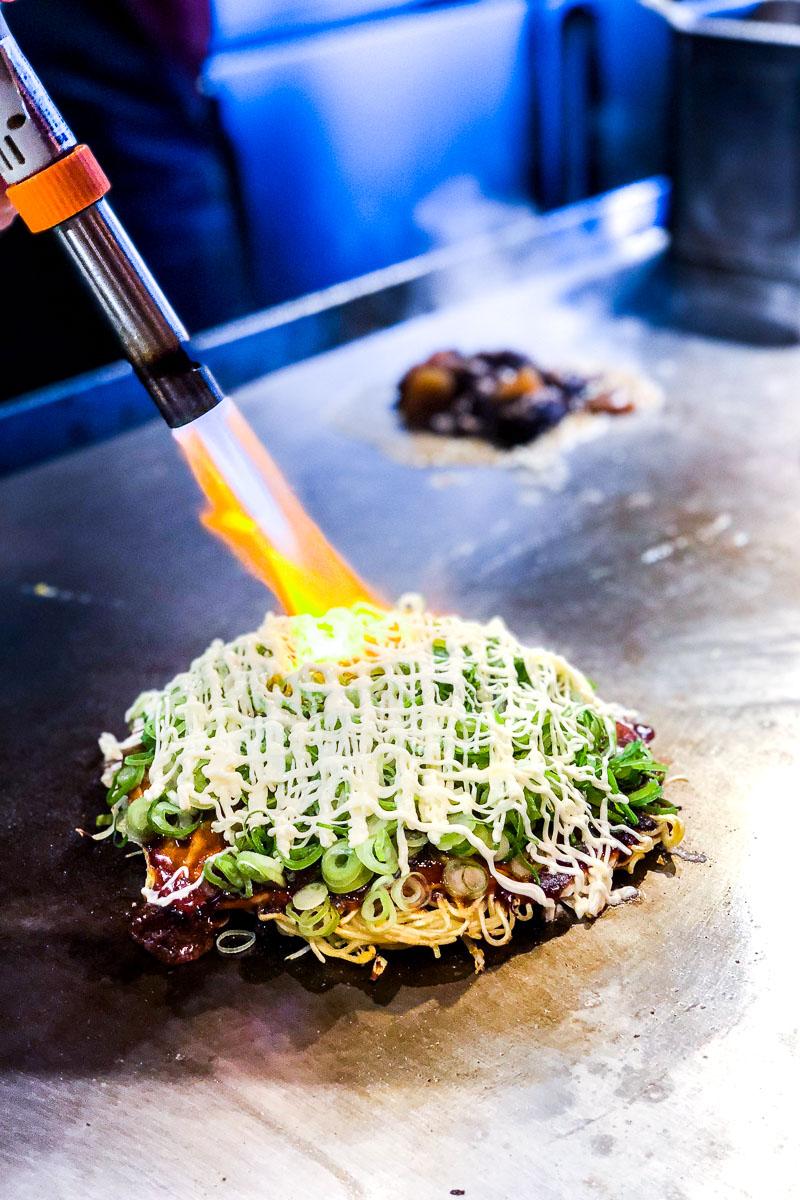 Mayonnaise auf Okonomiyaki Hiroshima Style wird mit Bunsenbrenner von Hand gegrillt