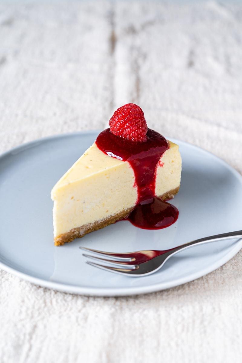 Stück New York Cheesecake mit Himbersauce und frischer Himbeere auf kleinem Teller