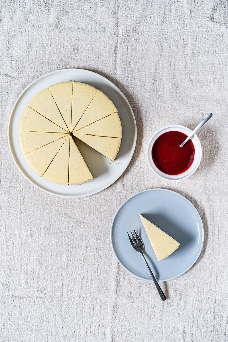 Stück New York Cheesecake auf kleinem Teller mit Schälchen Himbeersauce